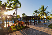 The sun setting through the palm trees and creates long shadows on the pool deck at this resort in Cuba, Varadero, Cuba