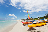 View looking down the white sand beach on a sunny day with kayaks and boats resting in the sand and people in the ocean in the distance, Varadero, Cuba