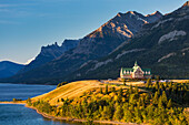 Prince of Wales hotel on hilltop at sunrise overlooking lake with mountain background and blue sky, Waterton, Alberta, Canada