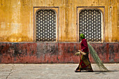 Woman with bamboo brushes in front of a building in the Galtaji temple, Jaipur, Rajasthan, India