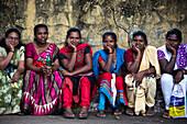 Six local women sitting on a wall, Thiruvananthapuram, Kerala, Indien