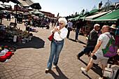 Woman walking in Jemaa el Fna market square, Marrakech, Morocco