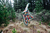 Quilt falling in forest