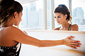 Mixed race dancer examining herself in mirror