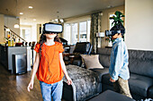 Mixed race children using virtual reality goggles in living room
