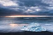 Iceberg at sunrise on Jokulsarlon Beach, a black volcanic sand beach in South East Iceland, Iceland, Polar Regions