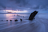 Shipwreck of the Helvetia on Rhossili Beach, looking towards Worms Head at sunset, Rhossili, Gower, Wales, United Kingdom, Europe