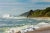 Surf breaking on sea stack and the Penon rock at this far south Nicoya Peninsula beach, Santa Teresa, Puntarenas, Costa Rica, Central America