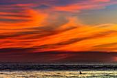 Lone surfer and sunset clouds off Playa Hermosa surf beach, southern Nicoya Peninsula, Santa Teresa, Puntarenas, Costa Rica, Central America