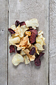 Directly above shot of potato and beetroot chips on wooden table