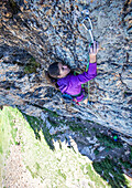 A women clips a quickdraw while lead climbing in Little Cottonwood Canyon, Utah.