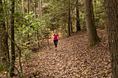 A young blonde woman runs on a trail in the forest in the fall in Tennessee