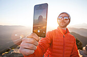 A man uses his smartphone to take a selfie while enjoying the outdoors just before sunset.