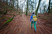 Blurred motion of a young active woman hiking through a dense forest