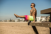 A shirtless male CrossFit athlete with a mohawk and tattoos wearing board shorts performs a L-sit on a lifeguard tower in Sunset Beach, California.