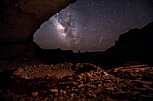 A meteor and the Milky Way drift across a clear, night sky above False Kiva in Canyonlands National Park.