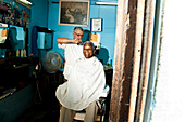 An elderly man smiles while getting his hair cut in a barber shop in Havana, Cuba.