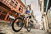 Caucasian man cycling on cobblestone street