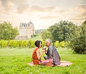Caucasian couple enjoying wine at picnic