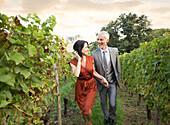Caucasian couple walking in vineyard