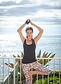 Mixed race amputee athlete practicing yoga on balcony