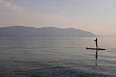 Caucasian woman standing on paddleboard in lake