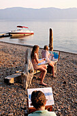 Caucasian family painting on remote lake