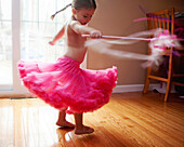 Caucasian girl twirling in skirt