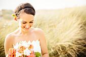 Caucasian bride standing in grass