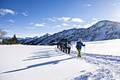 Ankommende Gruppe Schneeschuhwanderer mit Schatten im Schwarzwassertal bei Sonnenschein und Schnee, Vorarlberg, Österreich