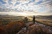A hiker on the peak of Geierstein near Lug, view over the Palatinate Forest, Palatinate Forest, Rhineland-Palatinate, Germany