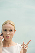 Woman making angry face while talking on cell phone