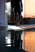 Man walking away from indoor pool, cropped