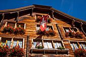 drapeau suisse flottant au balcon d'un chalet traditionnel dans le village d'andermatt, andermatt, canton d'uri, suisse