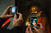 photo with camera and mobile phone in front of the portrait of jan six, visitor at the rembrandt exhibition, rijksmuseum, amsterdam, holland