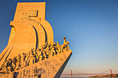the monument to the discoveries built in 1960 on the occasion of the 500th anniversary of the death of henry the navigator, prince of portugal, and the 25th of april bridge, lisbon, portugal