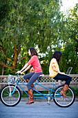 Stephanie Crocker and Trisha Leineke ride a tandem bike together. The woman on the back is surfing the internet on a laptop computer. Santa Cruz, California.