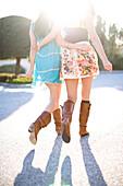 Waist down backlit image of Stephanie Crocker and Trisha Leineke walking across a parking lot. Santa Cruz, California.