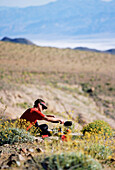 A backpacker stops to cook breakfast with a view of Death Valley. Death Valley National Park.