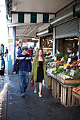 Adam Welch and Eliza Carlson walk through a section of the Pike's Place market in Seattle, Washington. The couple is out shopping on a beautiful day in the Pacific Northwest. Seattle, Washington.