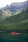Andy Feuling and daughter River paddle their kayak on Bowman Lake in   Glacier National Park, Montana.