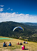 Poo Poo Point is a tourist attraction near Issaquah, WA where hang gliders launch into the clear sky above a thick green forest
