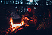 Mid adult man warming hands at campsite