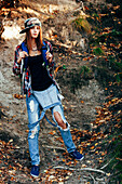 Full length portrait of fashionable young woman wearing torn jeans in forest
