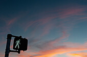 Walk signal with sunset in the background