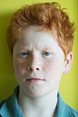 Boy with red hair furrowing brow, portrait