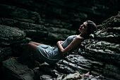 Caucasian woman laying on rock formation