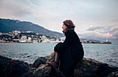 Caucasian woman admiring coastline from rock formation