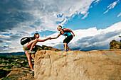 Woman helping friend climb rock formation