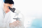 Mixed race scientist using microscope